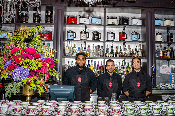 bartenders standing behind a bar covered in tea cups