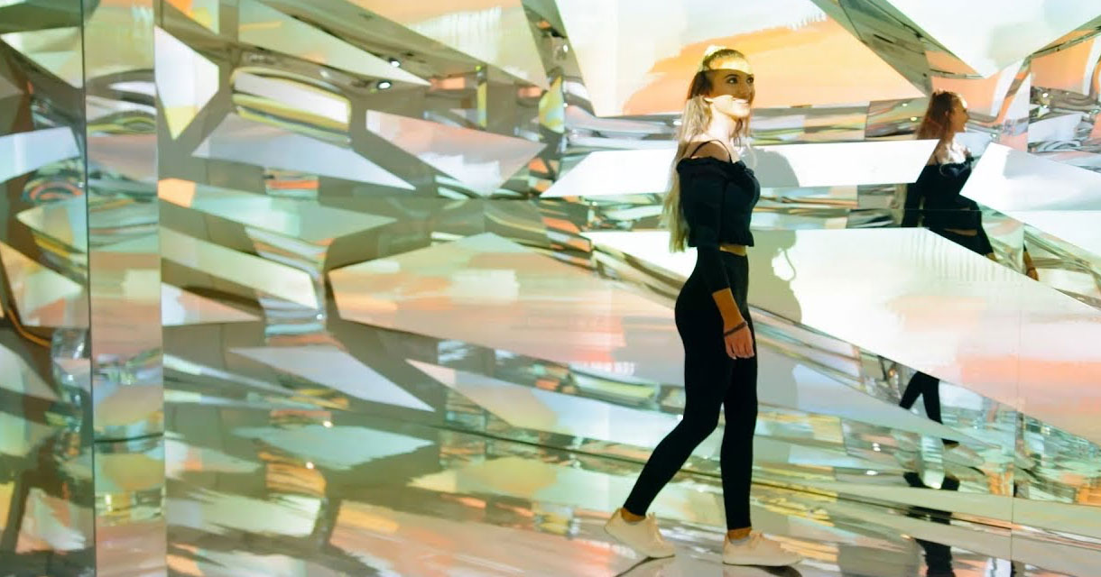 girl posing in a room full of mirrors