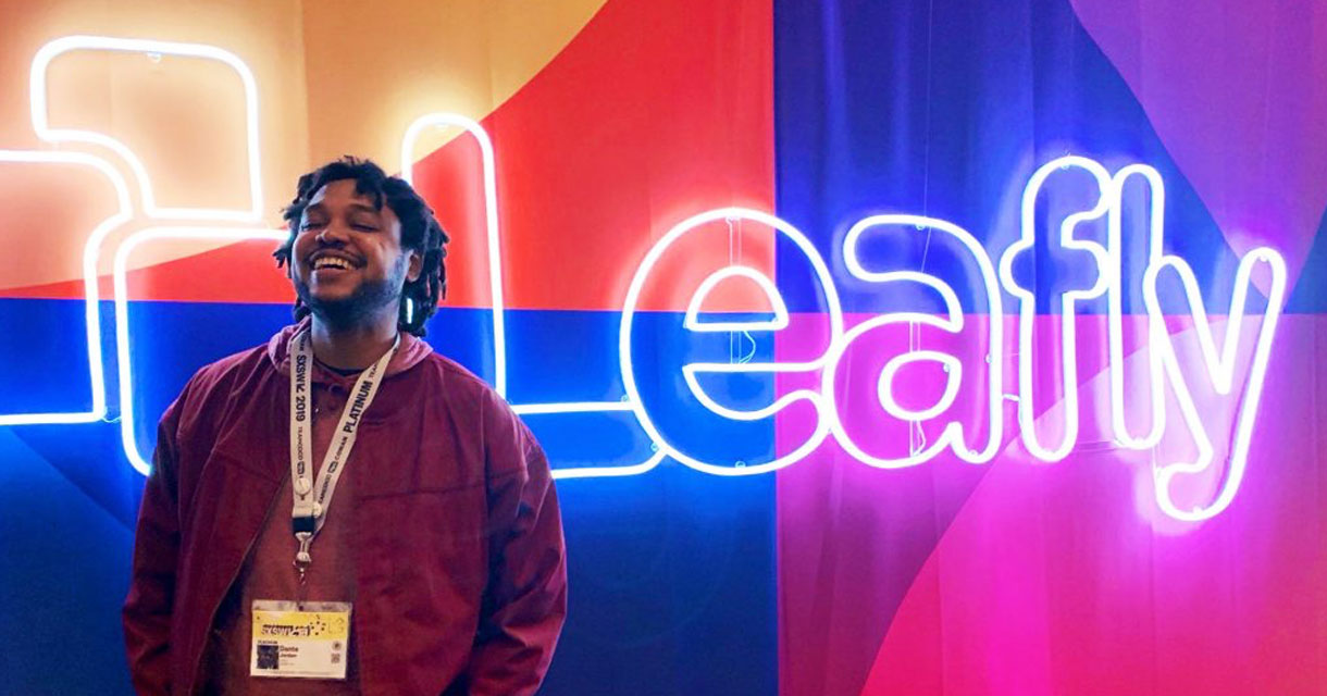 guy smiling in front of a leafly neon light sign