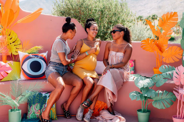 women sitting on a bench surrounded by colorful plants at an instagram coachella pop up experience