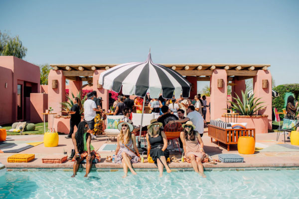 women sitting by the pool under a striped umbrella at an instagram coachella pop up experience