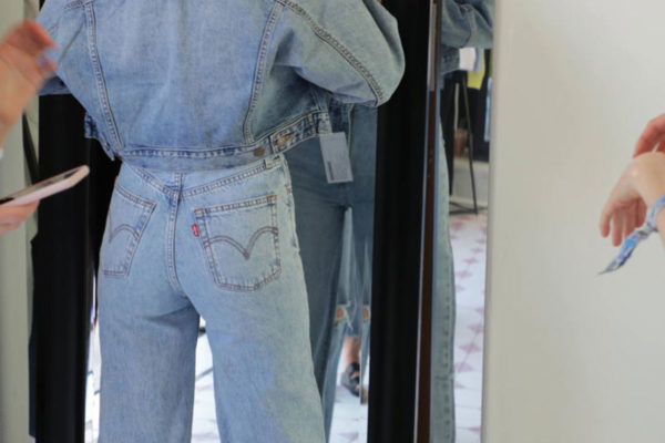 women looking in the mirror wearing levi jeans and a jean jacket