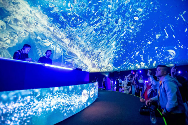dj's performing in an under water display with an audience