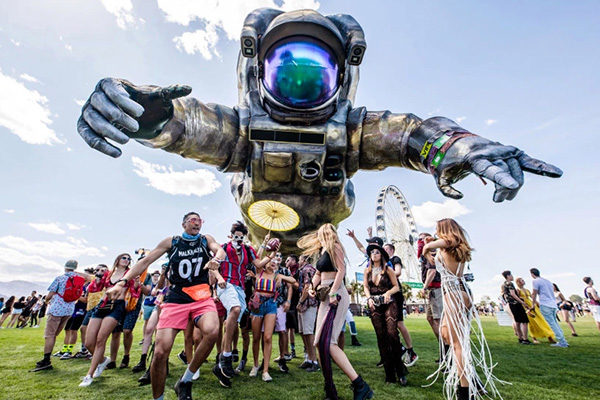 people posing with the poetic kinetics astronaut sculpture at coachella
