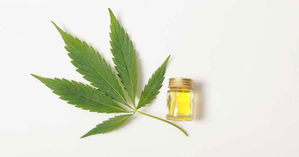 marijuana leaf next to a jar of oil on a white background