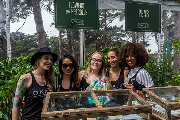 group of ladies at grass lands behind display of cannabis flowers prerolls and pens