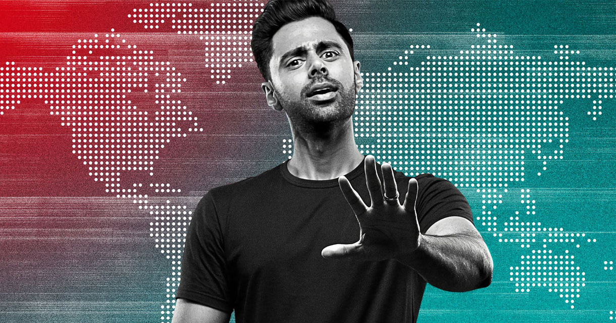 hasan minhaj posing in front of a red and blue map