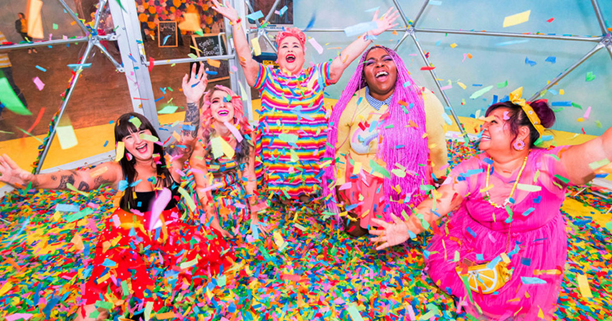 women posing in a pool of rainbow confetti