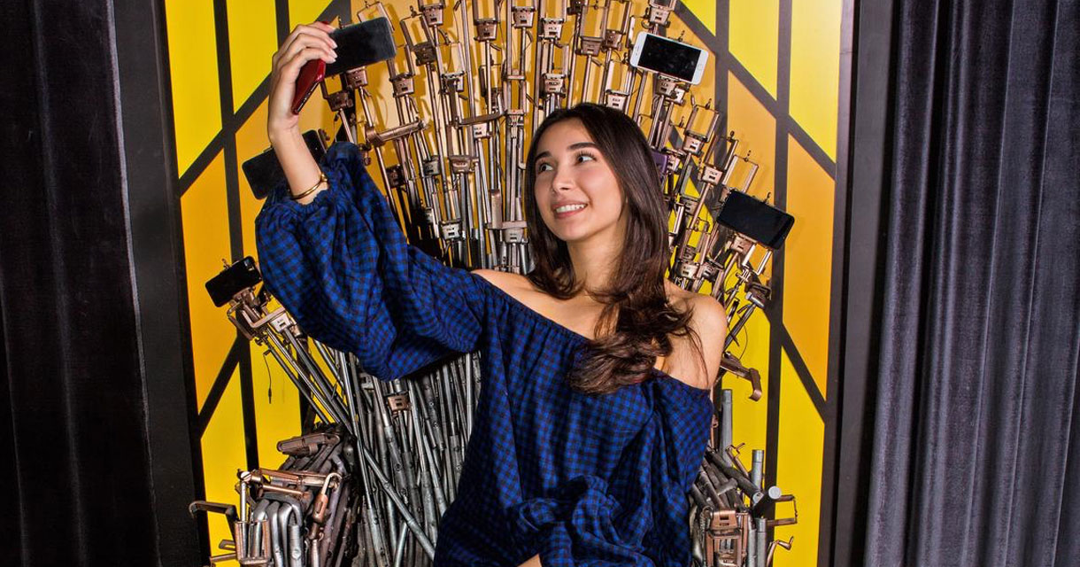 girl sitting on a throne of selfie sticks taking a selfie