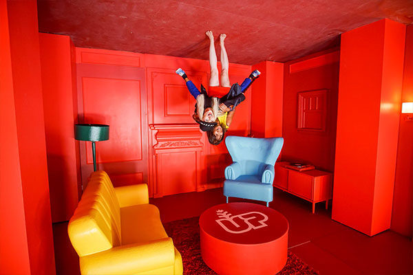 upside down house pop-up experience people on ceiling in a red room