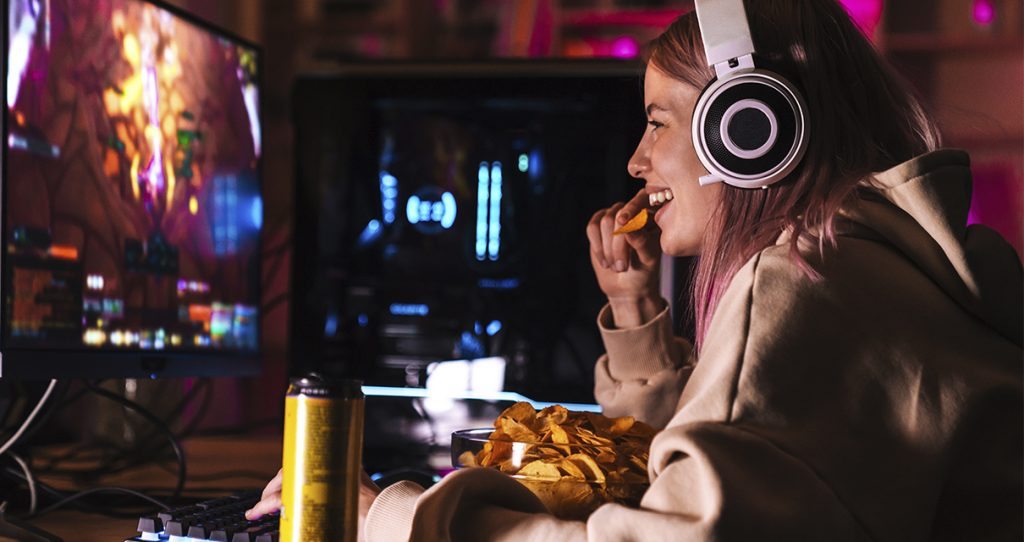 Girl with gaming headset watching an esports game on computer monitor while eating a snack