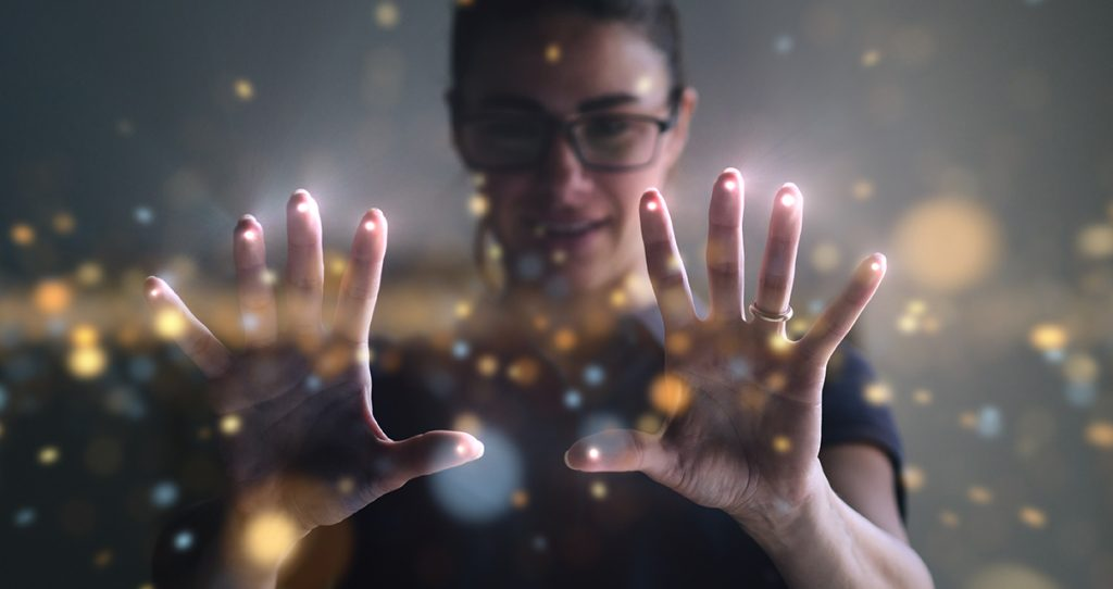 Person wearing glasses with hands spread open, overlayed with spots of light